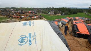 A Rohingya Muslim refugee walks through UNHCR tents at a refugee camp near the Bangladesh town of Gumdhum on September 17, 2017