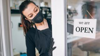 ai marketing 5g smartphones nanotechnology developments A woman in a face mask next to a sign on a shop door reading 'open'