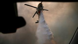 A helicopter makes a water drop as the Woolsey Fire burns in Malibu