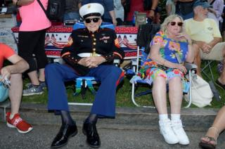 Retired veteran dressed in military uniform sits