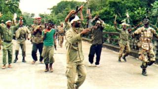 Fighters from United Liberation Movement (ULIMO) dey do war dance on top Po River bridge 02 September, 1992 for Monrovia.