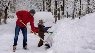 A man and boy shovelling snow
