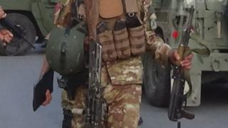 An Afghan soldier holds a gun