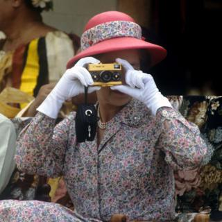 Taking photographs with her gold Rollei camera