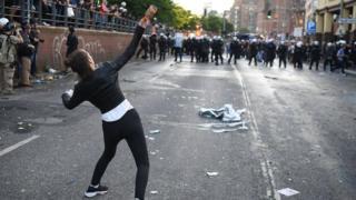 Una mujer arroja una botella.