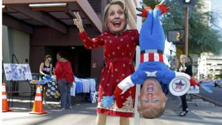 Person in Hillary Clinton mask holds inverted Donald Trump puppet, Phoenix, Arizona, 20 October 2016