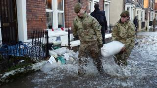 Members of the armed forces helping distribute sandbags to residents following flooding in Carlisle