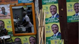 прохожий на фоне предвыборного плаката одного из кандидатов - Джуда Селестина
