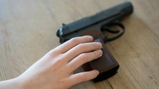 Mão de criança encosta em revólver colocado sobre mesa