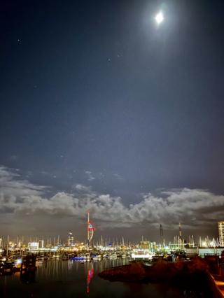 Boats in a harbour under moonlight