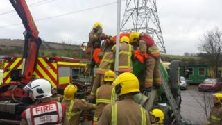 Firefighters lift the man free from the cement mixer