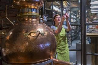 A woman working in a gin distillery