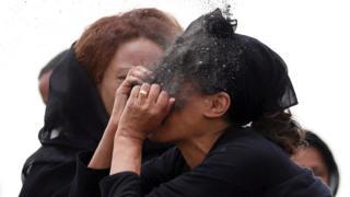 žena baca sebi u lice zemlju