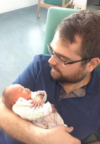 Richard Cox segurando sua filha recém-nascida