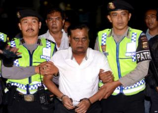 Rajendra Sadashiv Nikalje in handcuffs being led by two police officers