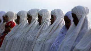A row of women robed in white close their eyes during a service in Banda Aceh