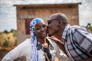 Julius kisses his wife on the cheek.