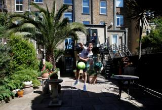 A tennis player serves a tennis ball in his garden