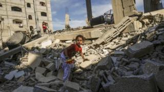 Uma menina palestina sobe nos destroços de um prédio que foi destruído por um ataque israelense em 5 de maio