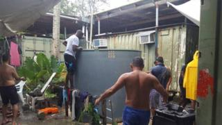 Asylum seekers and detainees at Manus Island around a water tank