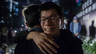 A man cries after laying a flower during a vigil in Hong Kong on 10 November, 2019, in memory of university student Alex Chow