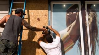 Tayler Hofe (trái) và Crew Hayes gia cố lại cửa sổ một cửa hàng ở Avon, Bắc Carolina, khi cơn bão Dorian đổ bộ ngày 5/9/2019