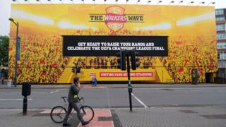 A cyclist walking his bike past a massive billboard in Cardiff