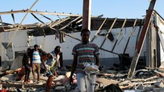 이민자들이 공습 뒤 잔해를 정리하고 있다