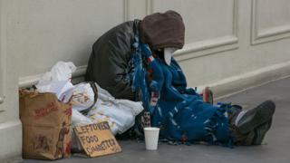 Una persona sin hogar pide dinero en una calle en Estados Unidos.