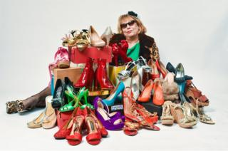 A women surrounded by a pile of shoes