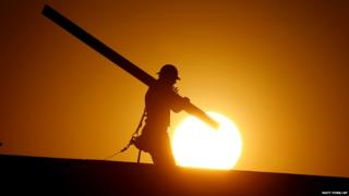 A man is silhouetted as the sun rises behind him