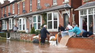 People bail water out of flooded homes after the River Wye burst its banks in Ross-on-Wye, western England, on February 17, 2020,