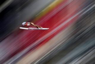 Dawid Kubacki is seen on skis in mid-air