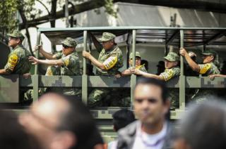 Mexican troops pictured in a vehicle wear a telltale yellow armband that shows they are responding to a disaster