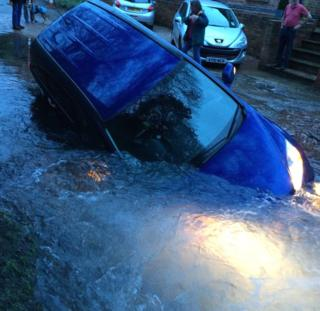 Car in a sinkhole created by a burst water main