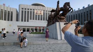 Tourists pose for photos in front of the Children's Palace in Pyongyang