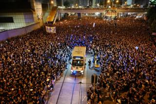 in_pictures An ambulance is pictured surrounded by thousands of protesters dressed in black during a new rally against a controversial extradition law proposal in Hong Kong on 16 June 2019