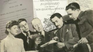 Integrantes del Servicio Latinoamericano de la BBC revisando un libreto para transmisión en 1947, con documentos relevantes a la versión radiofónica de Don Quijote en el fondo