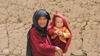 Elderly woman carrying a baby in Afghanistan
