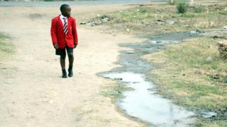 A schoolboy in a red blazer uniform in Chitungwiza, Zimbabwe - Monday 24 October 2016