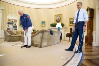 Bill Murray, left, putts a golf ball into a drinking glass in the Oval Office, as Barack Obama looks on