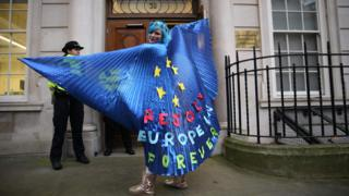 A pro-EU activist wearing a cape decorated with an EU flag design joins a rally organised by civil rights group New Europeans outside Europe House, central London on 31 January ,2020