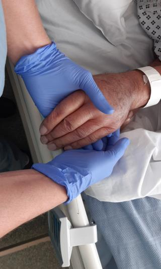 A nurse holds the hand of a Covid-19 patient
