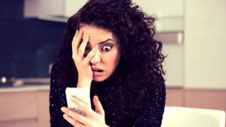 Mujer mirando un teléfono celular con actitud angustiada.