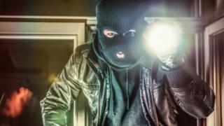 Masked burglar holding torch