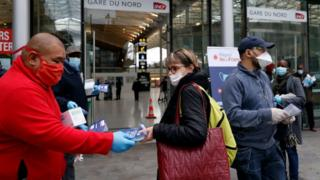 Volunteers distribute face masks and leaflets to commuters in front of the Gare du Nord train station in Paris on April 29, 2020,