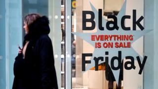 Người mua sắm vượt qua một dấu hiệu quảng cáo để giảm giá bán hàng 'Thứ Sáu Đen', bên ngoài một cửa hàng trên Phố Oxford ở London, vào ngày 26 tháng 11 năm 2019