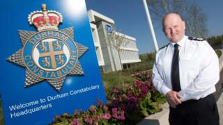 Mike Barton stands next to a Durham Constabulary logo