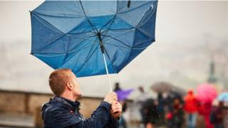 A man holding an umbrella caught by wind