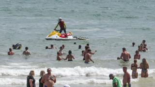 People enjoy the warm weather on Bournemouth beach. Met Office said Friday is the third hottest UK day on record as temperatures reached 37.8C at Heathrow Airport.